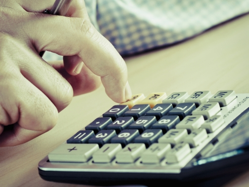 Close-up of a man's hand using a calculator